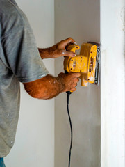 Worker with an orbital sander smoothes a wall