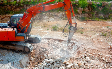 Close up of a heavy duty construction industry excavator machine crushing stones in a construction site