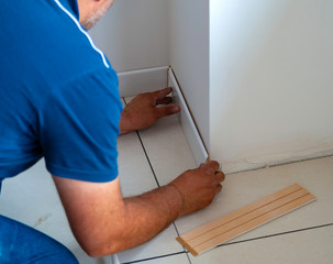 worker applies glue on wooden skirting board for wall mounting