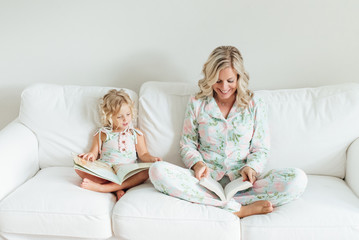 Mother and daughter reading a book while sitting on a sofa