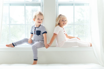 Brother and sister holding hands while sitting on a window sill