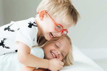 Blond brother hugging his sister on bed