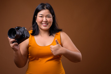 Keuken foto achterwand Fitness Beautiful overweight Asian woman photographer smiling and giving thumb up