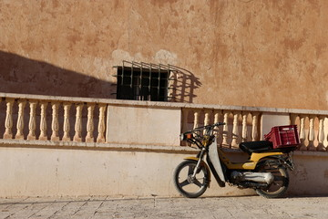 a motorbike in a street in desert old town Bou Saada, Algeria