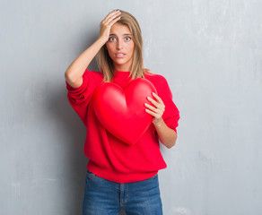 Beautiful young woman over grunge grey wall holding red heart stressed with hand on head, shocked with shame and surprise face, angry and frustrated. Fear and upset for mistake.
