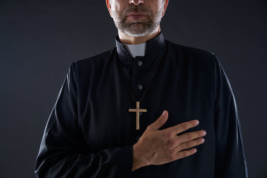 Priest hand in heart gesture with cross