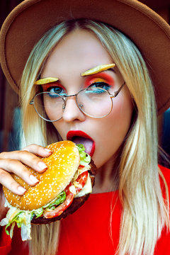 Stylish young lady in red with burger