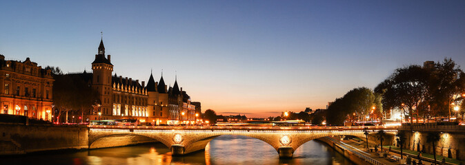 Panorama of Conciergerie and Illuminated bridge Pont au Change at night, Paris.
