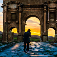 Photographer in front of a ancient Roman arch gate