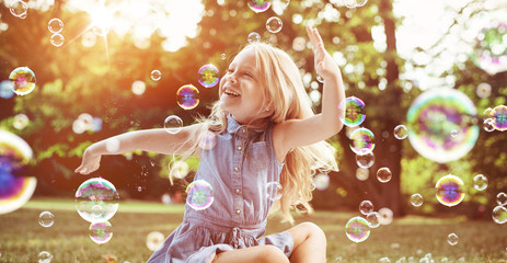 Foto op Plexiglas Artist KB Little blond girl among lots of flying bubbles