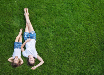Photo sur Plexiglas Artiste KB Conceptual portrait of a mother relaxing with daughter on a fresh, green lawn