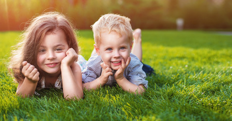 Photo sur Plexiglas Artiste KB Cheerful siblings relaxing on a fresh lawn