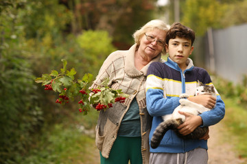 grandmother with grandson with viburnum and cat close up photo