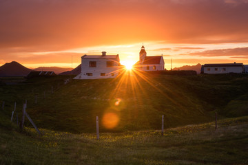 Amazing summer sunset landscape, Iceland. Flowering countryside with small church and sun, travel background