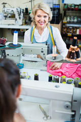 positive middle-aged woman tailor using sewing machine