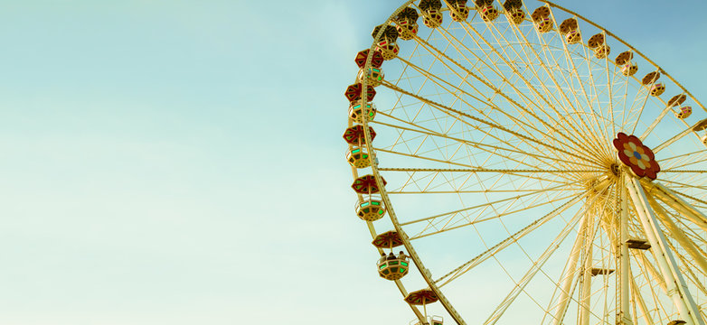 Ferris wheel (or wonder wheel) in an amusement park on a sunny summer day with blue sky and almost no clouds. Photo color toned for vintage retro look with yellow tones and light cyan sky in panorama