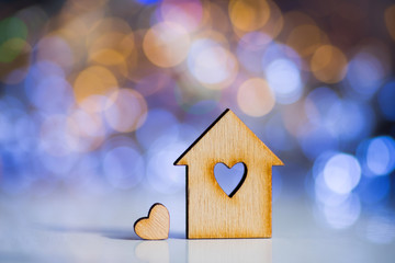 Wooden icon of house with hole in the form of heart with little heart on colorful bokeh background.