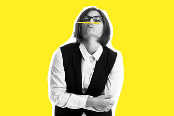 woman holding pen between nose and lips creative yellow background