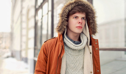 Wall Mural - Fashion portrait man walking in winter city in brown jacket with hood, knitted sweater