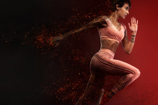 Fitness and sport motivation.. Strong and fit athletic, woman sprinter or runner, running on red background in the fire wearing sportswear.