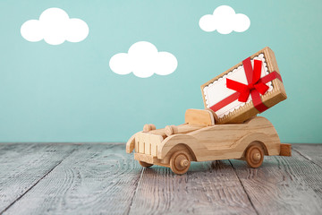 wooden vintage toy car with a red box gift on a blue with clouds background and wooden table