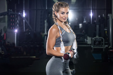 Beautiful young girl blonde, athlete bodybuilder, does exercises with dumbbells. In the modern gym, in beautiful sportswear. The concept is strength, beauty, diet, sports nutrition, sportswear, health