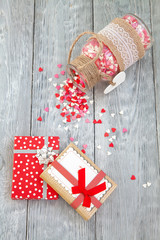 Christmas gifts with colorful hearts on wooden background