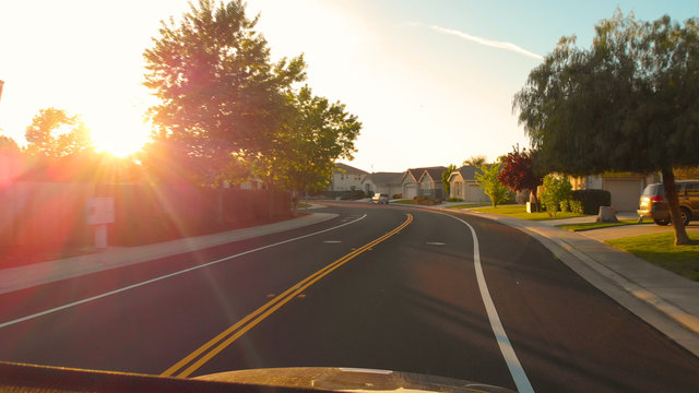 POV: Driving through the tranquil suburban neighborhood in California at sunset.
