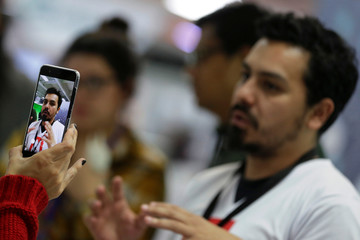 """A woman records a video with a cell phone at the digital summit of the orange economy """"Colombia 4.0"""" in Bogota"""