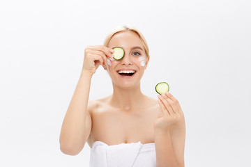 Portrait of the playful girl covering an eye by a slice of a cucumber, isolated on white.