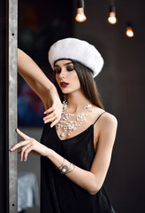 woman in white winter fir hat cap  in expensive loft restaurant touching wall with finger