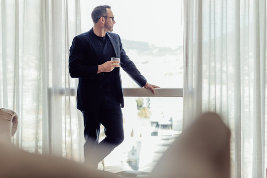 Businessman standing by a hotel room window