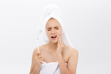 Young caucasian woman with toothache while brushing her teeth