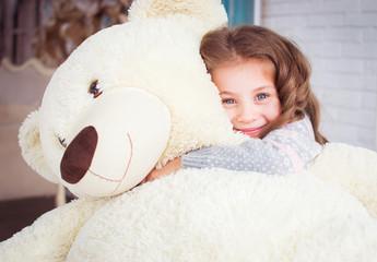 A child is hugging a big teddy bear. Happy girl hugging a soft toy.