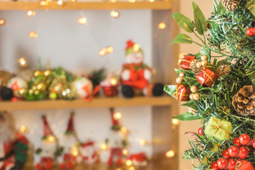 Close-up of Christmas tree with colorful ornaments in the foreground and Christmas decoration blurred in the background