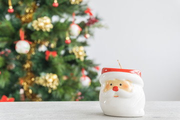 Santa Claus candle in the foreground and Christmas tree in the background