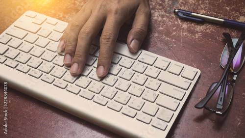 Wall mural Close up of a man hands working with a keyboard in office