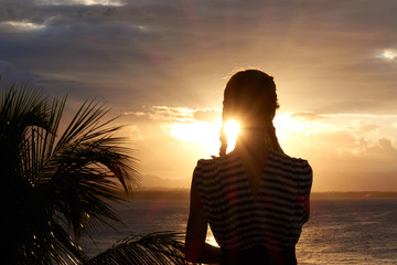 silhouette of young woman at sunset. watching the sunset