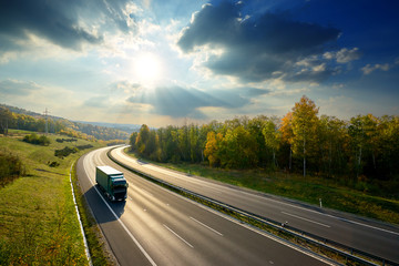 Fotobehang - Green truck driving on the asphalt highway between deciduous forest in autumn colors under the radiant sun and dramatic clouds. View from above.