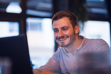 Young smart businessman working on laptop