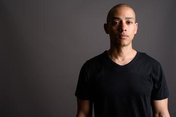Handsome bald man wearing black shirt against gray background