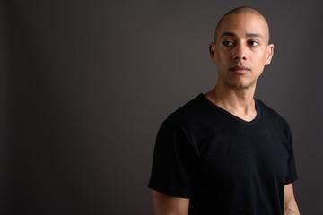 Handsome bald man wearing black shirt while thinking