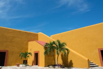 pared amarilla con cielo azul y palmeras campeche méxico