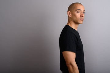 Profile view of handsome bald man looking at camera