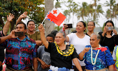 People wave as the royal motorcade carrying Meghan, Duchess of Sussex, and Britain's Prince Harry, Duke of Sussex, travels in Tonga
