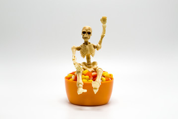 Halloween skeleton sitting on top of an orange bowl filled with candy corn isolated on a solid background