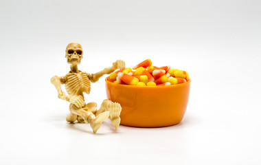 Halloween skeleton sitting next to an orange bowl filled with candy corn isolated on a solid background