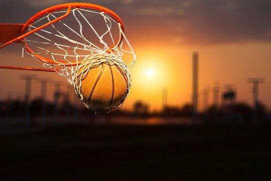 Basketball ball falling into net on sunset background