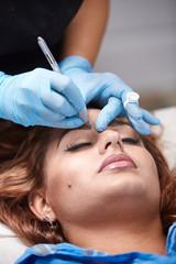 microblading close up, eyebrow adding pigment into skin.