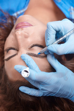 microblading close-up, hands adding pigment to eyebrows.